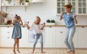 Happy,Mother,And,Kids,Dancing,And,Frolicking,Barefoot,On,Wooden
