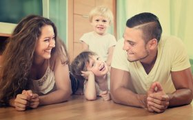 Happy,Smiling,Family,Of,Four,Enjoying,Time,In,Living,Room